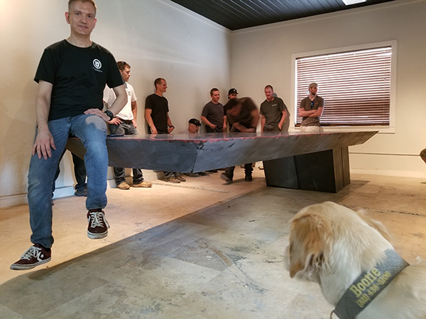 Jeff Girard sitting on edge of 11 foot cantilevered concrete table