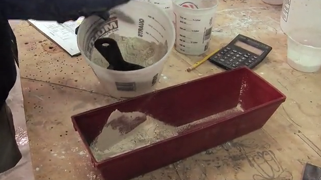 mixing cement grout in red mortar tray