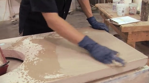 wiping grout onto concrete countertop
